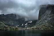 It rained most of the morning at my campsite on Lost Twin Lake in the Cloud Peak Wilderness. The cold rain was at times accompanied by thunder and lightning, gusty winds, and graupel (snow pellets). Nearby waterfalls grew louder and the sound of a distant rock slide echoed across the lake. My plan of summiting Darton Peak would have to wait for another day. After the last rain shower, the clouds descended and obscured the highest peaks. I took this picture while enjoying a cup of hot coffee as the rain finally stopped. It's difficult to convey just how massive these cliffs are. The sheer granite walls rise 1-2 thousand feet above the lake. If you can see the white speck at the base of the cliff on the right, that is a tent. The top of this bowl-shaped valley, known as a cirque, was carved out by glaciers long ago.