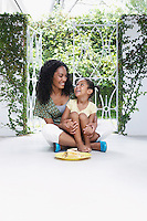 Mother and daughter (5-6 years) sitting on verandah floor