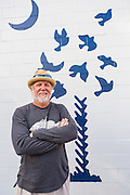 Artist Gil Shuler creator of the Charleston Strong design stand by his artwork during the inauguration of the Charleston Strong wall mural October 21, 2015 in Charleston, South Carolina. The artwork came to symbolize the unity of the city following the mass shooting at the historic Mother Emanuel African Methodist Episcopal Church last June.