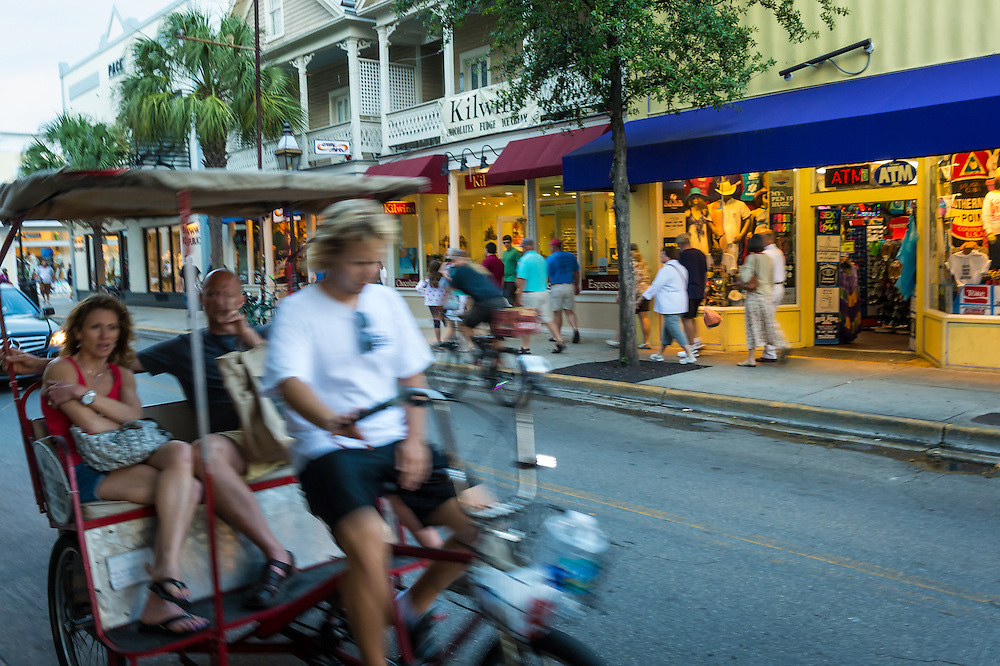 KEY WEST, FL - CIRCA 2012: Tourists in a Ricksaw in Duval Street in Key West circa 2012. The tropical city is a popular tourist destination with over 2 million yearly visitors.