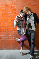 Young couple leaning on brick wall