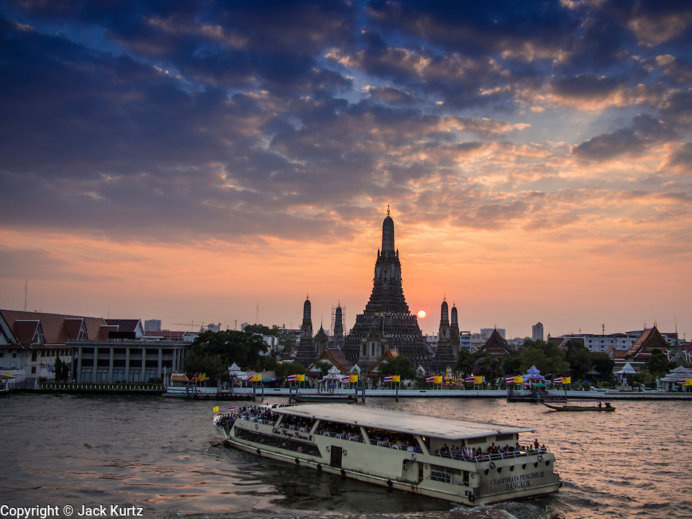 "19 DECEMBER 2013 - BANGKOK, THAILAND:  A tour boat in front of Wat Arun at the end of the day. Wat Arun Ratchawararam Ratchawaramahawihan or Wat Arun (""Temple of Dawn""), a Buddhist temple (wat) in Bangkok Yai district of Bangkok, on the Thonburi side of the Chao Phraya River. The temple derives its name from the Hindu god Aruna, often personified as the radiations of the rising sun. Wat Arun is among the best known of Thailand's landmarks and the first light of the morning reflects off the surface of the temple with pearly iridescence. Although the temple had existed since at least the seventeenth century, its distinctive Khmer style prang (spires) were built in the early nineteenth century during the reign of King Rama II.        PHOTO BY JACK KURTZ"