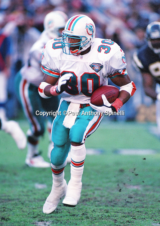 Miami Dolphins running back Bernie Parmalee (30) runs the ball during the NFL AFC Divisional playoff football game against the San Diego Chargers on Jan. 8, 1995, in San Diego. The Chargers won the game 22-21. (©Paul Anthony Spinelli)