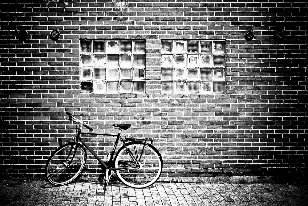 A bicycle beside a brick wall