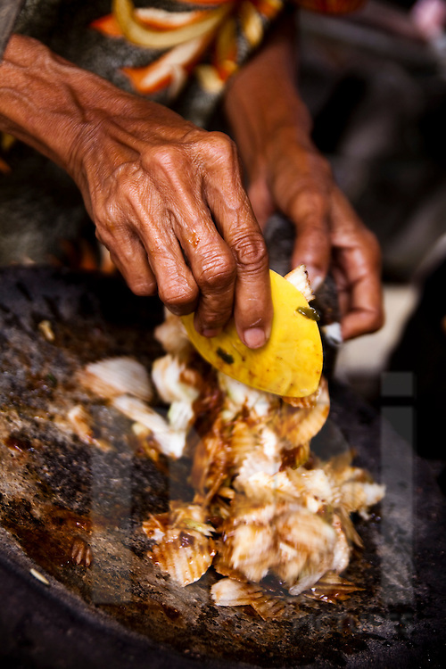 An elderly woman makes traditional street food in Ubud, Bali, Indonesia, Southeast Asia