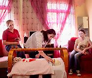 EN : Megi,16, taking care of her newborn baby in the house she shares with her husband and parents in law. Most of the child spouses lives with their parents-in-law since the beginning of their marriage and some experience a great deal of stress and pressure from the mother-in-law. <br /> Batumi, Adjara region, Georgia, 2016.<br /> <br /> SP: Megi cuida de su hija de cuatro meses, Ana Maria. Megi se casó en el otoño de 2015 con un joven de 18 años que había conocido un mes antes en las redes sociales.