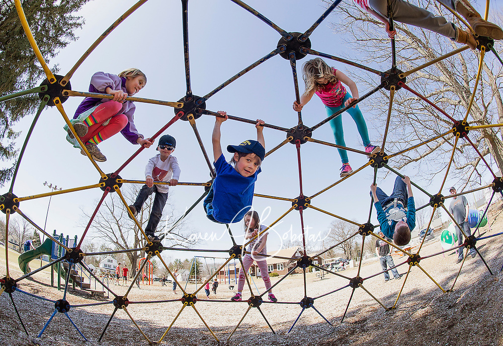 Xavier Morrison along with several youngsters take to the jungle gym to bask in the warmth of Spring on Sunday afternoon at Leavitt Park.  (Karen Bobotas/for the Laconia Daily Sun)