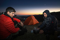 Hikers (Adrian Grancea, left & Dan Dinu) heating up water in front of their tent on a rocky limestone ridge in Mehedinti Plateau Geopark, Geoparcul Platoul Mehedinți, Romania.