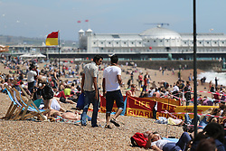 © Licensed to London News Pictures. 13/07/2014. Brighton, UK. People relaxing relax in the sunshine on Brighton seafont. Temperatures in the UK are expected to hit record highs for the year this week. Photo credit : Hugo Michiels/LNP