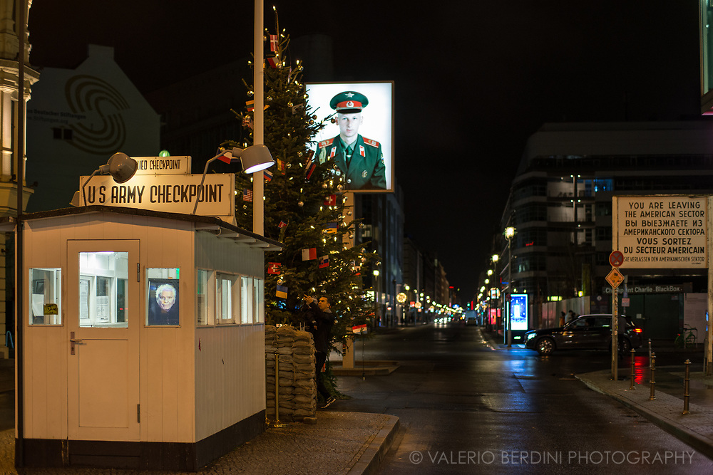 Fictional rendering of Checkpoint Charlie, the main crossing point between East and West Berlin during the Cold War is now a touristic hotspot, filled with souvenir shops and fast food restaurants.