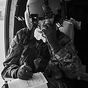 A flight paramedic catches a quick bite while conducting in-flight equipment checks.