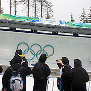 "Winter Olympics, Vancouver, 2010.Spectators, dressed in penguin suits find vantage points to watch the action during the Bobsleigh Four-man competition  at The Whistler Sliding Centre, Whistler, during the Vancouver Winter Olympics. 25th February 2010. Photo Tim Clayton..'BOB'..Images from the Four-man Bobsleigh Competition. Winter Olympics, Vancouver 2010..History was made at the Whistler Sliding Centre when the USA four-man bobsleigh team, led by Steven Holcomb took the Gold. The first time since 1948, a gap of 62 years, since the USA have won an Olympic Bobsleigh gold and they did it with their sleigh named ""Night Train""...The four days of practice and competition show the tension, nervousness and preparation as the teams of hardened men cope with the challenge of traveling at average speeds of over 150 km an hour. Indeed, five teams had already pulled out of the event before the opening heats because of track complexity, speed and fear, and on the final day, another four teams did not start after six crashes in the first two heats...Teams warm up behind the start complex, warming muscles in the cold in preparation for the explosive start. Many teams prepare in silence, mentally preparing themselves as they wait at the top of the run, in the bobsleigh sheds and the loading areas for their turn. When it's time to slide each team performs it's own starting ritual, followed by the much practiced start out of the blocks for just over four seconds, the teams are then in the hands of the accomplished drivers as they hurtle down the track for just over fifty seconds...Spectators clamber for the best position on track to see the sleighs for a split second, many unsuccessfully try to capture the moments on camera, The rumble of the sleigh is heard then the crowds gasp as it hurtles past in a blur...The American foursome of  Steven Holcomb, Justin Olsen, Steve Mesler and Curtis Tomasevicz finished with a pooled four-heat time of 3min 24.46sec. The German team led by Andre"