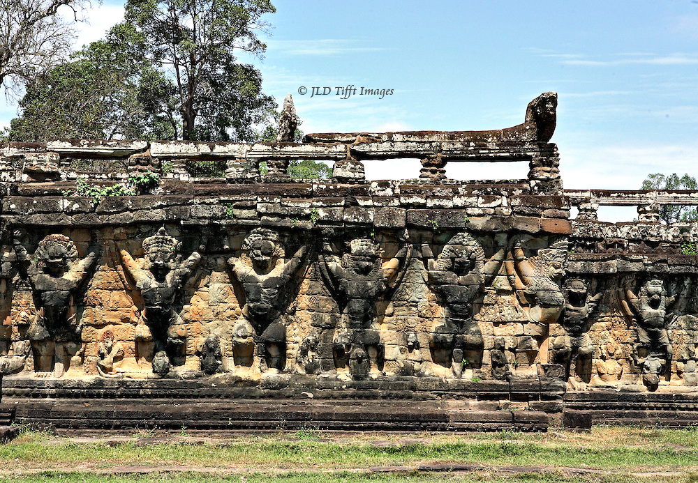 Angkor Thom: supporting wall of terraces of the elephants held up by a row of squatting caryatids in high relief. Top of the wall is uneven and Naga balustrade above broken in places, as the structure slowly deteriorates.