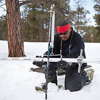 Ralphus Begay, a hydrologic technician with the Navajo Nation Department of Water weighs a sampling tube before he starts measuring snowpack at the Whiskey Creek SNOTEL site in the Chuska mountains, Tuesday, Jan. 29.
