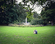 A man reading in the grass with a fountain in the background.
