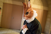 A man dressed as a rabbit with a ruff collar waits for the elevator.