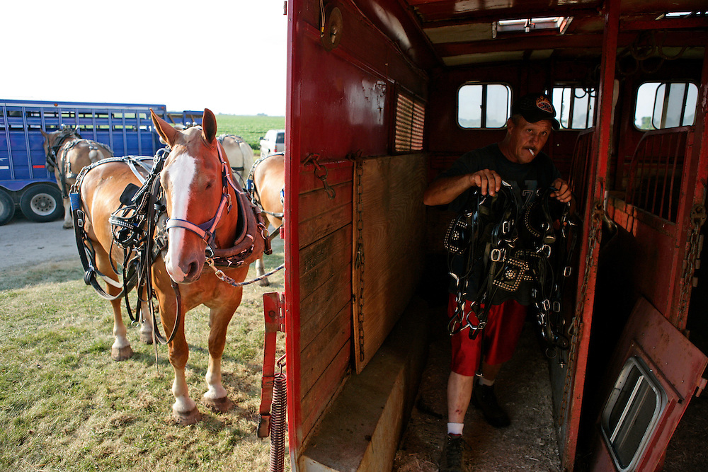 "Charlie Beeman in his trailer before the horse pulling competition at the Mercer County Fair in Aledo, IL on Thursday, July 14.  Along with his brother, Roger, and friend, Bud, Charlie traveled over 700 miles from Nashville, Michigan for the competition.  All three men horse pull full-time as loggers and they compete whenever they can.  ""Anywhere we wanna go, we cut out with them,"" says Charlie."