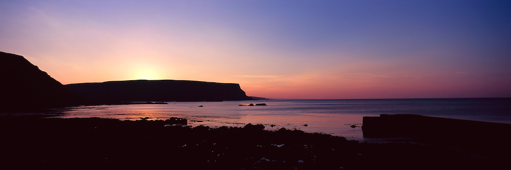 The headland above the town of Gardenstown in Gamrie bay at dusk on the remote north east coast of Aberdeenshire