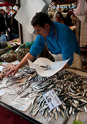 Fishmonger selling sardines at fish market near Rialto Bridge in Venice italy