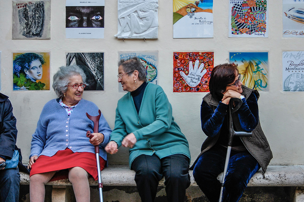 Women chatting near public art. Montalcino, Italy