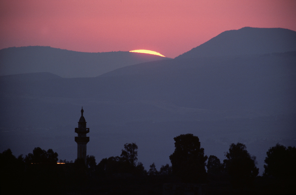 Israel, Golan Heights, Sun sets behind minaret in Arab village abandoned after 1967 Six Day War
