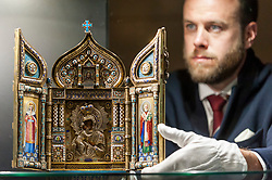 "© Licensed to London News Pictures. 01/06/2018. LONDON, UK. A Sotheby's technician presents ""An Imperial Silver-Gilt and Enamel Triptych Icon of the Feodorovskaya Mother of God"", 1894, by Savelev Brothers (Est. GBP80-120k) at a preview of the Russian Pictures and Russian Works of Art, Fabergé & Icons sale which will take place at Sotheby's, New Bond Street on 5 June.  Photo credit: Stephen Chung/LNP"