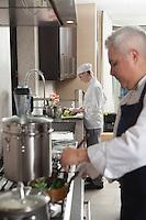 Chef heating pan on hob