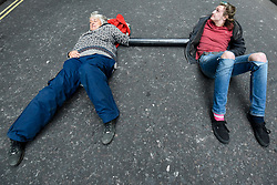 © Licensed to London News Pictures. 10/10/2019. LONDON, UK. A couple, arms secured by plastic pipe, lay on the ground of Northumberland Avenue off Trafalgar Square during day 4 of Extinction Rebellion's climate change protest in the capital.  Activists are calling on the Government to take immediate action against the negative impact of climate change.  Photo credit: Stephen Chung/LNP