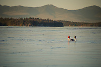 A couple of ice fisherman head off the ice in the Broads on Lake Winnipesaukee Monday afternoon as the sun starts to set.  (Karen Bobotas/for the Laconia Daily Sun)
