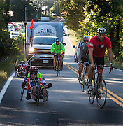 The riders trailed by the support vehicle climb a hill in Virginia.