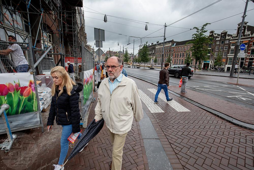 Voetgangers passeren een bouwplaats op het Rokin in Amsterdam.<br /> <br /> Pedestrians pass a construction area at the Rokin in Amsterdam.