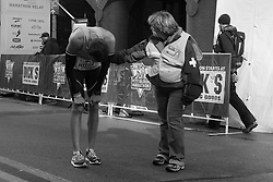 A medical team member offers a runner assistance after he shows signs of distress while crossing the finish line.