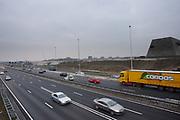 Verkeer raast langs de tunnel (uiterst rechts) bij de A2 in Utrecht. Het college van B en W in Utrecht heeft de vergunning verleent om de tunnel op de A2 open te stellen. Door meningsverschillen tussen de autoriteiten over de veiligheid was de tunnel nog steeds gesloten. Om de doorstroom te bevorderen was de snelweg tijdelijk met twee rijstroken verbreed voor 30 miljoen euro, de tunnel zelf heeft vijf rijstroken. De tunnel wordt gefaseerd in gebruik genomen, halverwege het jaar moet al het verkeer door de tunnel rijden.