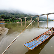 A long, thin wooden boat is moored by bamboo poles along the sandy shores of the Nam Ou (River Ou) in Nong Khiaw in northern Laos.