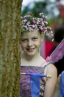 A young shy fairy at the annual Filberg Festival peeks out from behind a tree.  Comox, The Comox Valley, Vancouver Island, British Columbia, Canada.
