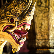 A gold naga at Wat Xieng Thong (Temple of the Golden City) on the northern tip of the peninsula of Luang Prabang, Laos. Originally built around 1560, the temple was the main site for royal coronations and remains ones of the most important temples in Laos.