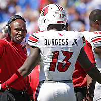 After UK almost scored, U of L head coach Charlie Strong talks over the play with UofL linebacker James Burgess in the third quarter as the University of Kentucky plays the University of Louisville at Commonwealth Stadium in Lexington, Ky. Saturday Sept. 14, 2013. Louisville beat Kentucky 27-13. Photo by David Stephenson