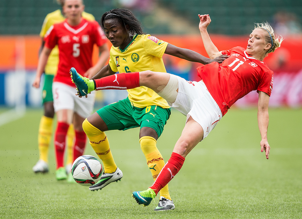 Cameroon's Francine Zouga (L) and Switzerland's Lara Dickenmann  collide during their FIFA Women's World Cup group C match at Commonwealth Stadium in Edmonton, Canada on June 16, 2015. Cameroon defeated Switzerland 2-1.  AFP PHOTO/GEOFF ROBINS