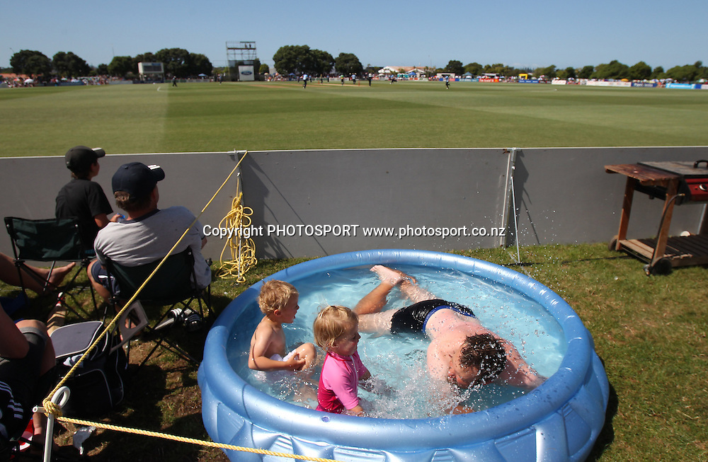 Groundsman with his children enjoys the swimming pool on the boundary the Twenty20 Cricket, HRV Cup Final 2010/11. Auckland Aces v Central Stags, Colin Maiden Park, Auckland. Sunday 2 January 2011. Photo: Andrew Cornaga/photosport.co.nz