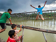 15 SEPTEMBER 2014 - SANGKHLA BURI, KANCHANABURI, THAILAND: Children jump off the temporary bamboo bridge that is being used while the Mon Bridge (in the background) is repaired. The 2800 foot long (850 meters) Saphan Mon (Mon Bridge) spans the Song Kalia River. It is reportedly second longest wooden bridge in the world. The bridge was severely damaged during heavy rainfall in July 2013 when its 230 foot middle section  (70 meters) collapsed during flooding. Officially known as Uttamanusorn Bridge, the bridge has been used by people in Sangkhla Buri (also known as Sangkhlaburi) for 20 years. The bridge was was conceived by Luang Pho Uttama, the late abbot of of Wat Wang Wiwekaram, and was built by hand by Mon refugees from Myanmar (then Burma). The wooden bridge is one of the leading tourist attractions in Kanchanaburi province. The loss of the bridge has hurt the economy of the Mon community opposite Sangkhla Buri. The repair has taken far longer than expected. Thai Prime Minister General Prayuth Chan-ocha ordered an engineer unit of the Royal Thai Army to help the local Mon population repair the bridge. Local people said they hope the bridge is repaired by the end November, which is when the tourist season starts.    PHOTO BY JACK KURTZ