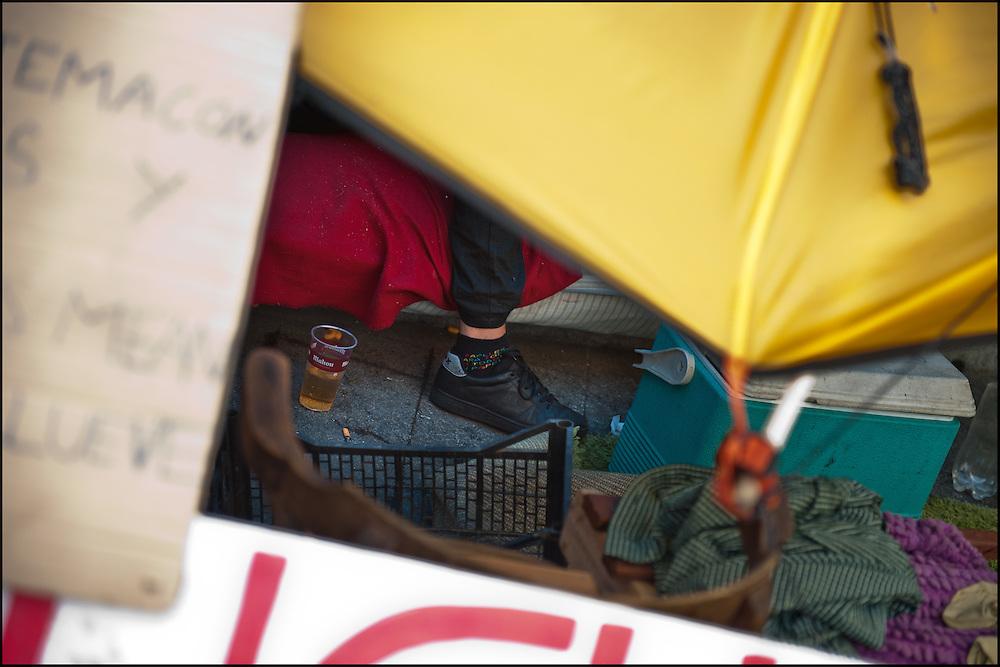 """Certains consomment de l'alcool sur le camp même si une majorite le deplore. // Le mouvement spontane du """"15 M"""" (15 mai) compose de citoyens espagnols campe depuis 2 semaines sur la place Puerta Del Sol avec pour revendication la construction d'une democratie nouvelle. Organise en commission les citoyens prennent la parole lors d'assemblee ouverte a tous - Place Puerta Del Sol à Madrid le Juin 2011. ©Benjamin Girette/IP3Press"""