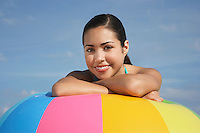 Teenage girl (16-17) sitting leaning on beach ball close up portrait