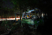 A bus wreck sit rotting away in Bangkok's 'car cemetery'. <br /> <br /> According to a 2014 study by the University of Michigan&rsquo;s Transportation Research Institute Thailand ranks number 2 in the world for road fatalities, narrowly second only to Namibia. The report found a frightening 44 road deaths were recorded per 10,000 population. The high accident rate is often attributed to reckless driving, including driving while intoxicated, and lack of safety precautions such as wearing a helmet on motorbikes. A WHO report indicated that 26 percent of road deaths in Thailand involve alcohol.<br /> <br /> The sheer number of crashed vehicles is so high that police now hold auctions to sell off the vehicles, either not wanted by their owner or beyond repair, and it has become a good business. But the auctions are a relatively new phenomenon where previously cars would be kept at police stations until the legal case is complete and then deposited at a collection site.<br /> <br /> On the outskirts of Bangkok in a scruffy suburb is one such depository. Dubbed &lsquo;the car cemetery&rsquo; by locals it was where many of Bangkok&rsquo;s damaged wrecks would end up if no-one else wanted to them. But the site has also taken on another reputation; that of being one of the most haunted places in the city, third to be precise according to a local TV station. Thai&rsquo;s are very superstitious people and most believe in ghosts or spirits. Here it was believed that the spirits of those killed in the crashes remained with the vehicles they died in. Many a passerby or taxi driver have stories of people in and around the compound who then simply vanishing. Locals became so frightened of the place that a group of Thai Buddhist monks from a nearby temple were invited in to perform a ritual exorcism to release the spirits.<br /> <br /> With most crashed cars now being bought at the auctions the car cemetery doesn&rsquo;t receive new vehicles anymore but many of the old ones remain surrounded by weeds and covered in rust. Grotesque relics and unwanted wr