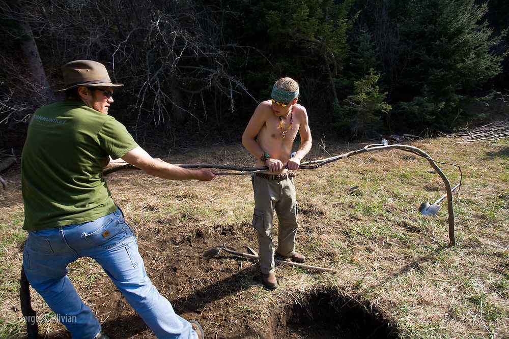 People preparing raw materials and building a sweat lodge in summer for a ceremony of the North American Church in Boulder, Colorado.