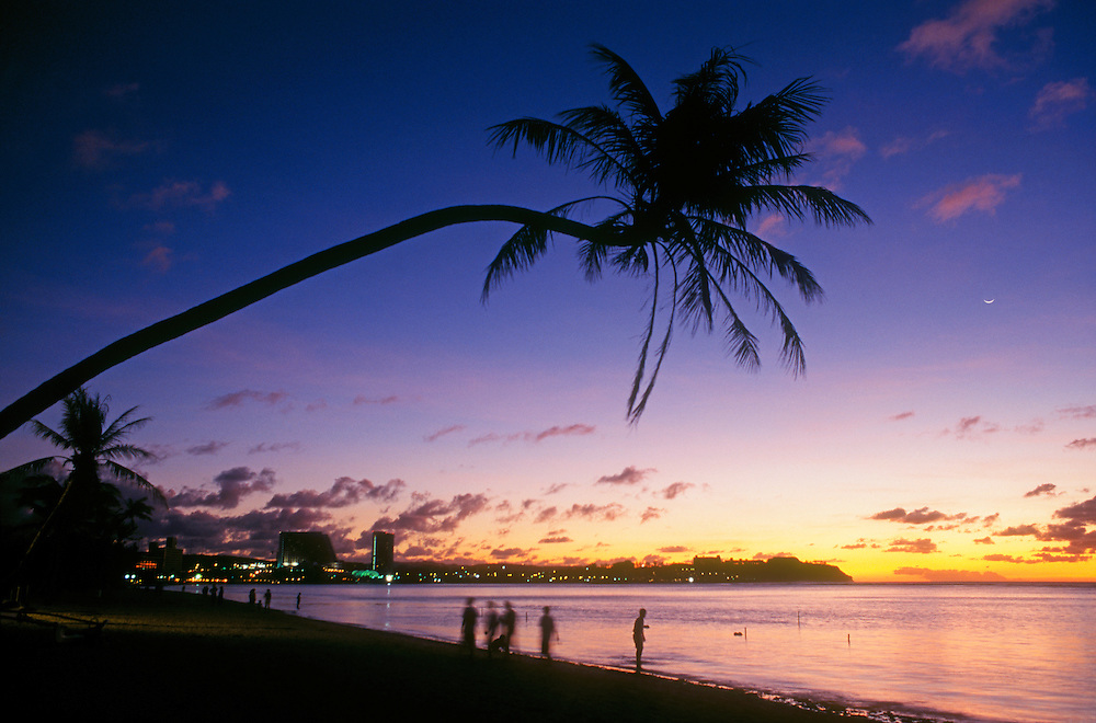 Twilight at Tumon Bay resort area with palm tree over beach; Guam, Micronesia.