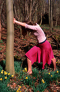 A912PA Young girl leaning against a tree in daffodil woods