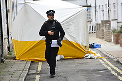 © Licensed to London News Pictures. 08/03/2019. Fulham, London, UK. A police officer passes in from of the tent erected over the spot 17yr old Ayub Hassan collapsed and later died of stab wounds sustained in an attack yesterday afternoon. Four teenagers have been arrested in connection with the murder, the investigation continues. Photo credit: Guilhem Baker/LNP