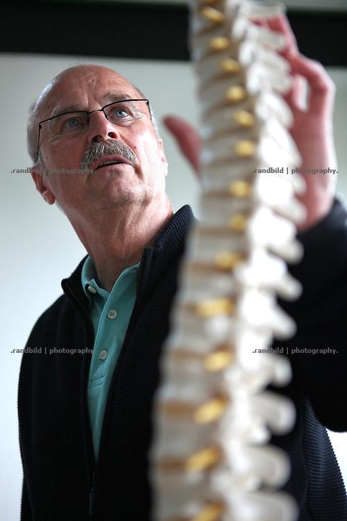 Landarzt Dr. Reiner Kretschmer blickt auf ein Modell einer Wirbelsäule in seiner Praxis in Gartow, Lüchow-Dannenberg.