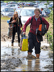 Festival-goers in the mud at one of the car parks at the Isle of Wight Festival  after heavy rainfall, Sunday June 24, 2012. Photo By i-Images