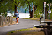 Aly Houghton of Coeur d'Alene goes for a training run out the Centennial Trail near Bennett Bay of Lake Coeur d'Alene on Sunday in preparation for next weekend's Ironman Triathlon.